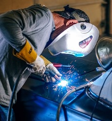 Oakman AL welder working on car